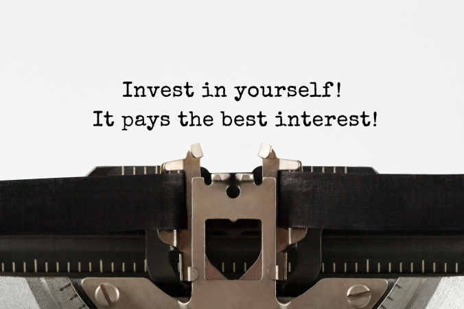 Invest in yourself, it pays the best interest text typed on retro typewriter